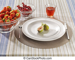 Table with red fruits on a plate