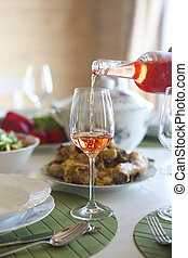 Table with rose wine, fish soup, salad and chiken