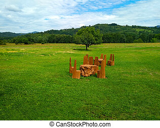 Table with solid wood chairs on a green lawn on a background of mountains, outdoor recreation