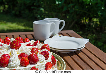 Table with strawberry cake and coffee cups in background
