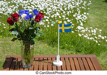 Table with summer flowers and a swedish flag