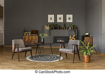 Table with tulips on rug between grey armchairs in retro living room interior with plant. Real photo