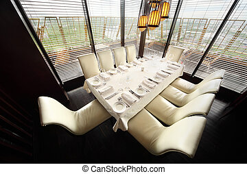table with white tablecloth and serving and ten white chairs...