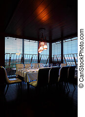 table with white tablecloth and serving and ten white chairs in empty restaurant at evening