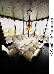 table with white tablecloth and serving and ten white chairs in empty restaurant