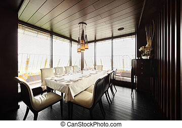 table with white tablecloth and serving and white chairs in empty restaurant