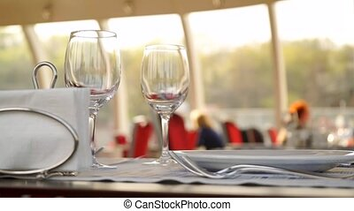 Table with wine glasses in river boat restaurant, Moscow river