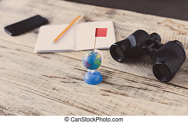 Table wooden plancs, smartphone, nootbook, pencil, Globe, binoculars, flag, aim, achieving, target, tourism, travel. Tourism. Hipster style. Top view with copy space. Free space for text.