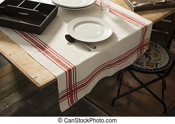 White tablecloth or linen designed with printed red stripes laid on a wooden table with a pair of spoons, a drinking glass, round plates, and utensil tray placed on top.