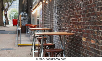 4k Video of two tables and four chairs on the sidewalk next to a red bricks wall, with trees and the street as background