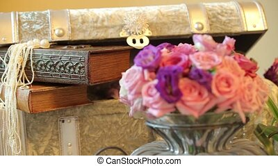 Hall's decorations of flowers on the tables, on the table there are flowers in a glass vase and trunk where is slightly ajar and inside it are two decorated books and bead necklace, dynamic change of focus, close up