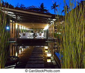 Tables on an open terrace among the tropical nature at night