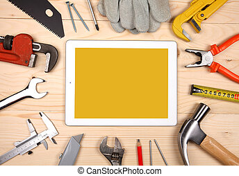 Tablet and set of plumbing and tools on the wooden table