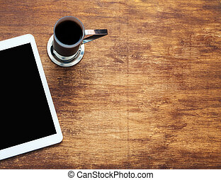 Tablet computer and coffee on wooden background. View from th top