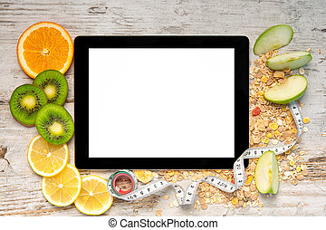 tablet computer on a wooden table with fruit and a measuring...