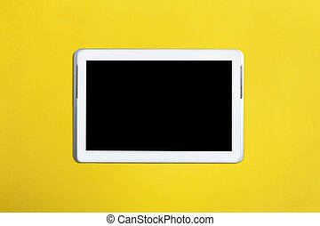 Tablet computer with black screen isolated on yellow surface