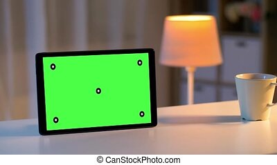 tablet computer with green screen on table at home -...