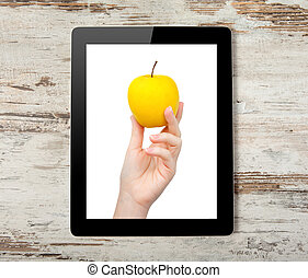 Tablet computer with the hand and a yellow apple on the screen