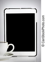 Tablet computer with white cup of coffee isolated on white background.