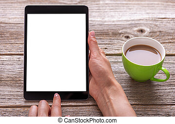 Tablet in hands on a wooden table with a cup.