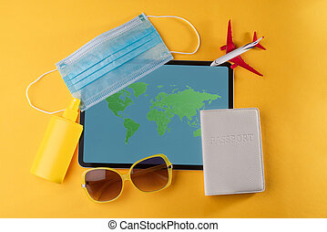 Tablet, medical mask, plane toy, passport, sunglasses and sunscreen spray