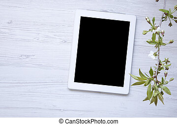 Tablet on a white wooden table decorated with blossoming cherry branch top view