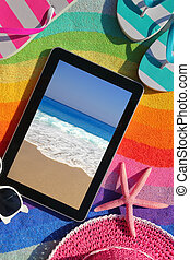 Tablet on beach towel with summer accessories