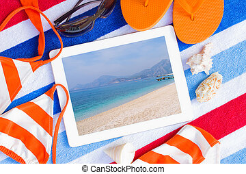tablet on  towels with sunbathing accessories