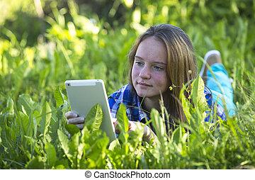 tablet., parc, jeune, jolie fille, herbe, mensonge