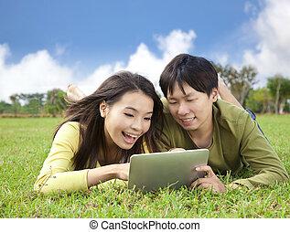 tablet, park, jonge, terwijl, computer, aziaat, student, gebruik, het liggen