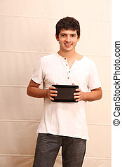 Tablet PC - A young, latin man with a Tablet PC, face in...
