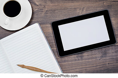 Tablet pc and a coffee and notebook with pen on the office