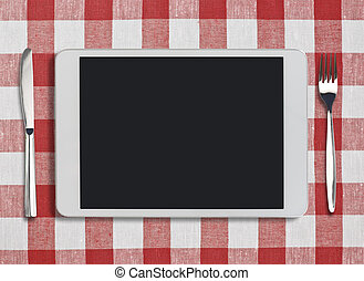 tablet pc, fork and knife on red checked tablecloth - white...