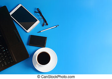 Tablet PC, laptop, pen, glasses and cup with black coffee on saucer on blue background