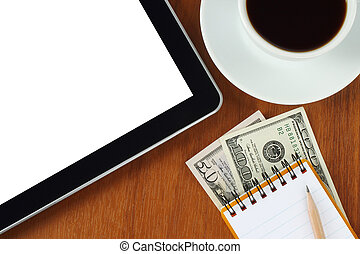 Tablet pc, notepad, pen, money and cup of coffee on wooden background close-up