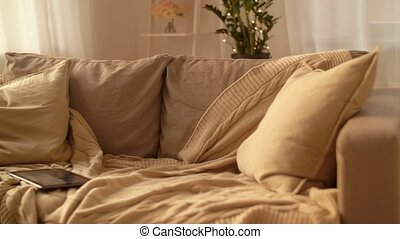 tablet pc on sofa at home living room - comfort, technology...
