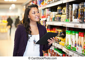 Tablet PC Shopping List - Smiling woman looking at the...