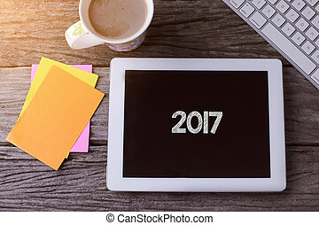 Tablet pc with 2017 and a cup of coffee on wooden background.