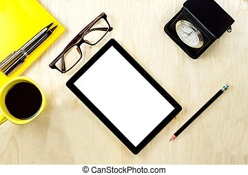 Tablet PC with blank white screen display and eyeglasses, cup of coffee and office supply on the wooden working table for business and education concepts.