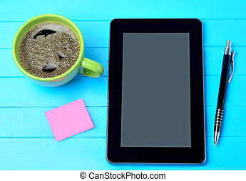 Tablet pc with coffee cup and notes on table