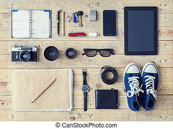 Outfit of a stylish traveler. Set of different objects and equipment: tablet, phone, album, glasses, camera, lenses, gumshoes, knife and watches.