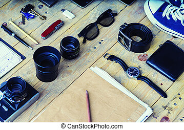 Tablet, phone, album, glasses, camera, lenses, gumshoes, knife and watches.