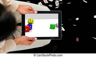 Tablet showing dices with Pokercards background Video