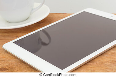 Tablet with blank black screen on wooden table with coffee cup