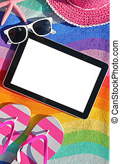 Tablet with blank screen on beach towel with accessories