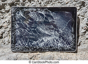 tablet with broken display on the stones