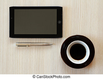 tablet with coffee on table