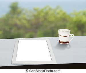 Tablet with cup of coffee on table with nature view