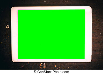 Tablet computer with green screen on wooden background