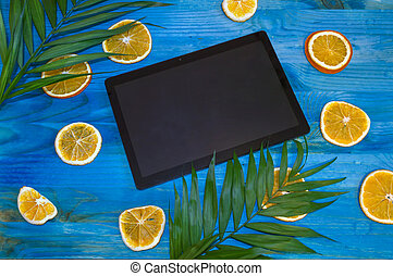 tablet with tropical fruits and palm leaves